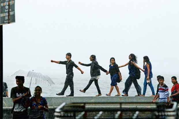 Teenagers enjoying the rains at the seafront on Marine Drive, Mumbai